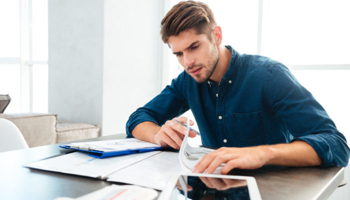Busy young man sitting at home and thinking about finances